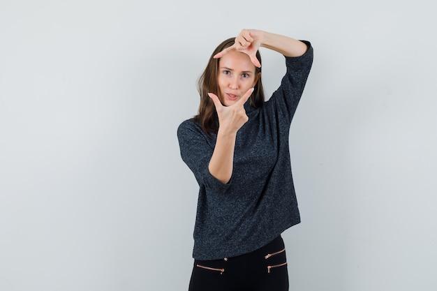 Молодая женщина в черной блузке показывает жест рамки и смотрит сосредоточенно
