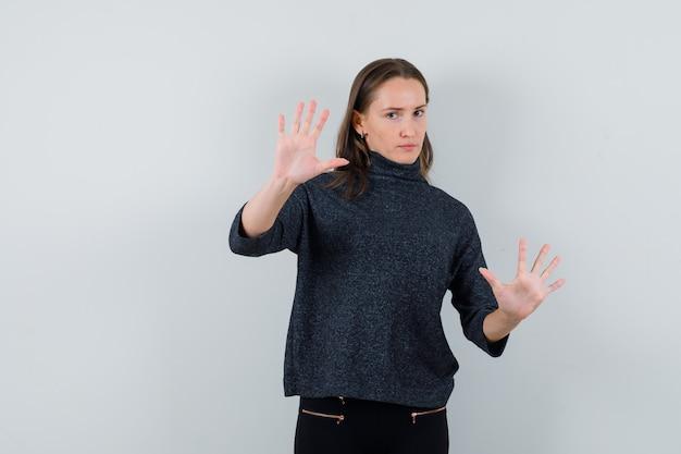 Молодая женщина в черной блузке показывает жест стоп и выглядит строго
