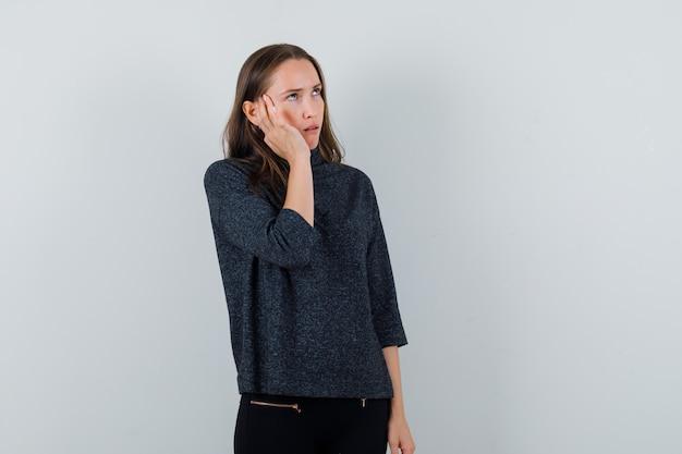 Молодая женщина в черной блузке трогает ее висок и выглядит странно
