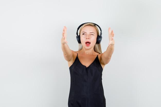 黒の一重項の若い女性、正面に手をつないで陽気に見えるヘッドフォン