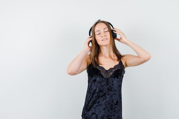 Молодая женщина в черной майке слушает музыку в наушниках и выглядит счастливой
