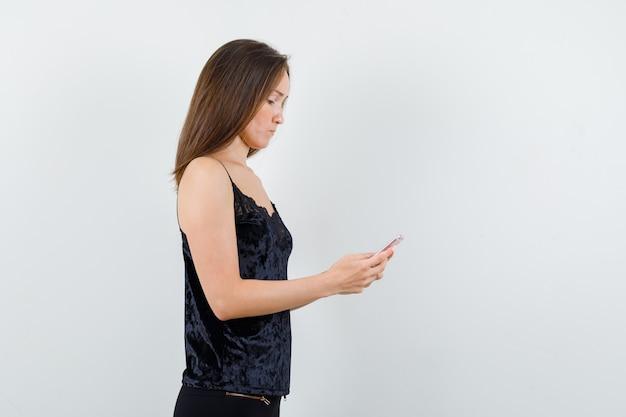 Молодая женщина в черной майке, штанах использует мобильный телефон и выглядит занятой