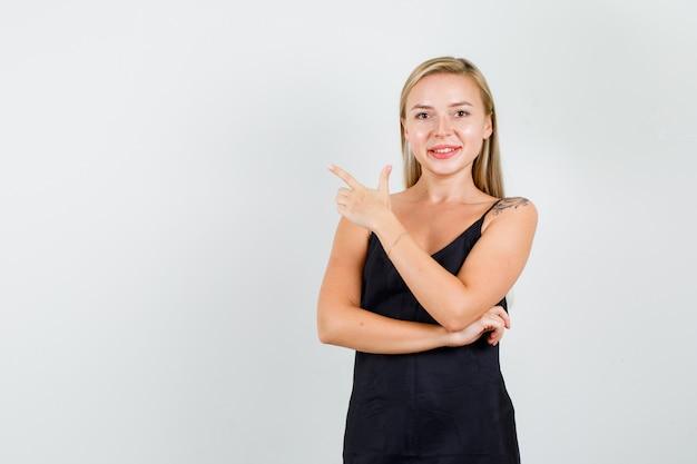 銃のジェスチャーで横を指して陽気に見える黒い一重項の若い女性