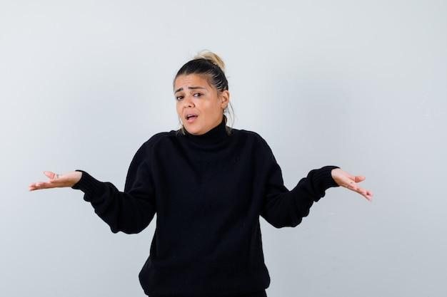 Молодая женщина в черном свитере с высоким воротом показывает беспомощный жест и выглядит невежественным, вид спереди.