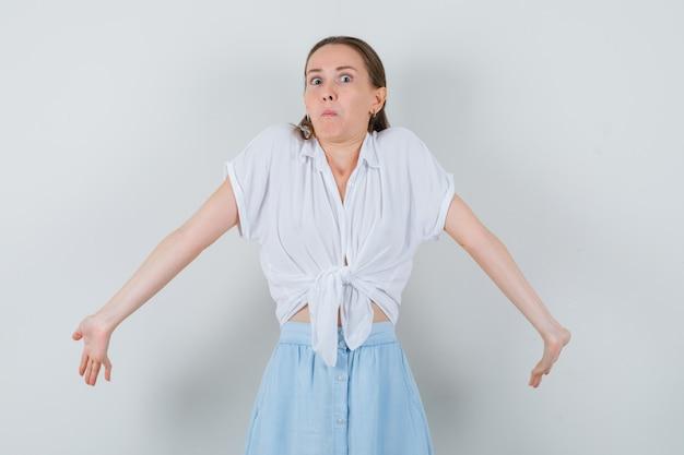 肩をすくめると混乱しているように見えることによって無力なジェスチャーを示すブラウスとスカートの若い女性