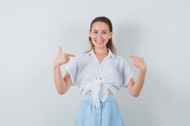 ブラウスを着た若い女性、スカートは自分を指差して嬉しそうに見える