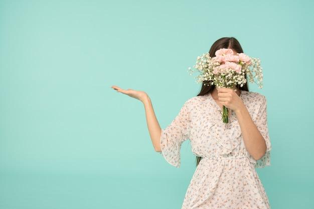 Молодая женщина в ярком платье скрывает лицо за букетом весенних цветов с раскрытой ладонью, изолированной на синем фоне