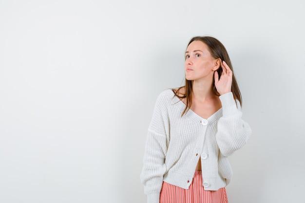 Молодая женщина в кардигане и юбке держит руку за ухом, выглядит любопытно изолированной