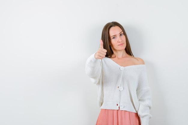 カーディガンとスカートの若い女性が自信を持って孤立しているように親指を上に表示