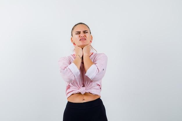 Молодая женщина в повседневной рубашке, взявшись за руки на шее и выглядящей измотанной, вид спереди.