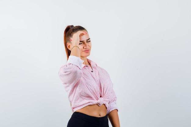 Молодая женщина в повседневной рубашке, штанах, держа руку на лбу и выглядящей измотанной, вид спереди.