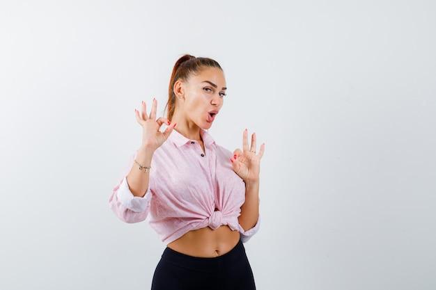Молодая женщина в повседневной рубашке, штанах показывает жест и выглядит счастливой, вид спереди.
