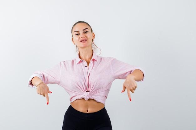 カジュアルなシャツを着た若い女性が下を向いて自信を持って、正面図。