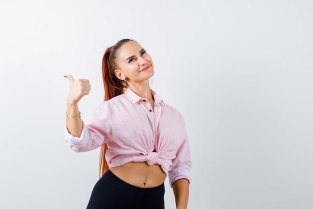 Молодая женщина в повседневной рубашке показывает палец вверх и выглядит счастливым, вид спереди.