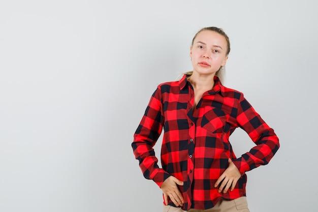 Молодая женщина в клетчатой рубашке, штаны позирует, стоя и красиво, вид спереди.