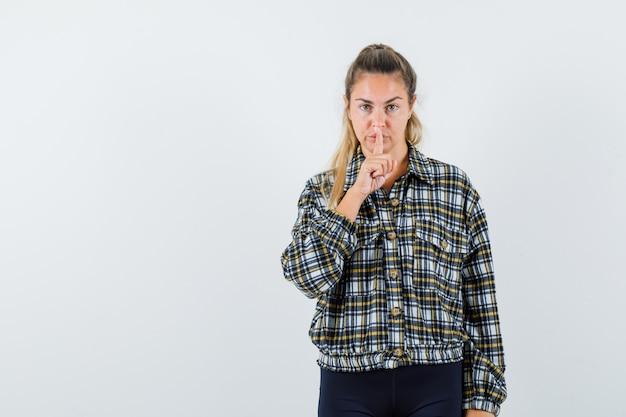 沈黙のジェスチャーを示し、真剣に見えるチェックシャツの若い女性、正面図。