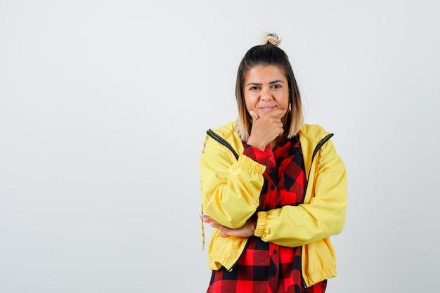 市松模様のシャツ、頬に指を保持し、陽気に見えるジャケット、正面図の若い女性。