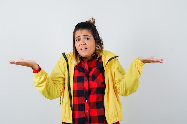 市松模様のシャツを着た若い女性、無力なジェスチャーを示し、動揺して見えるジャケット、正面図。