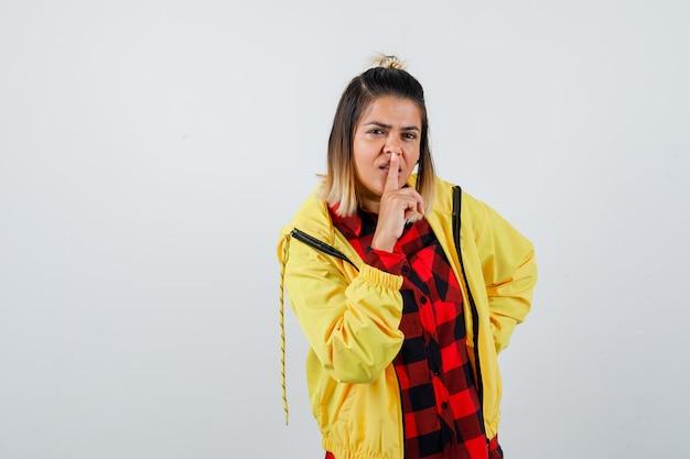 市松模様のシャツを着た若い女性、沈黙のジェスチャーを示し、焦点を当てて見えるジャケット、正面図。 無料写真