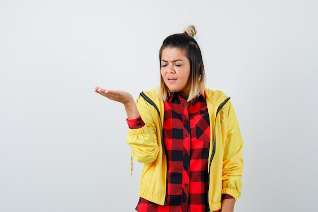 市松模様のシャツを着た若い女性、見下ろして元気がないように見ながら手のひらを横に広げているジャケット、正面図。