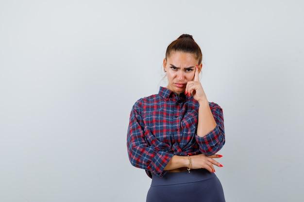 市松模様のシャツを着た若い女性、思考ポーズで立って物思いにふけるパンツ、正面図。
