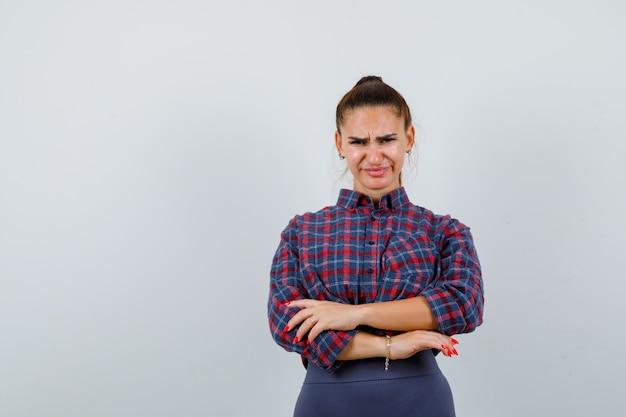 市松模様のシャツを着た若い女性、腕を組んで立っているパンツ、不機嫌そうな顔、正面図。
