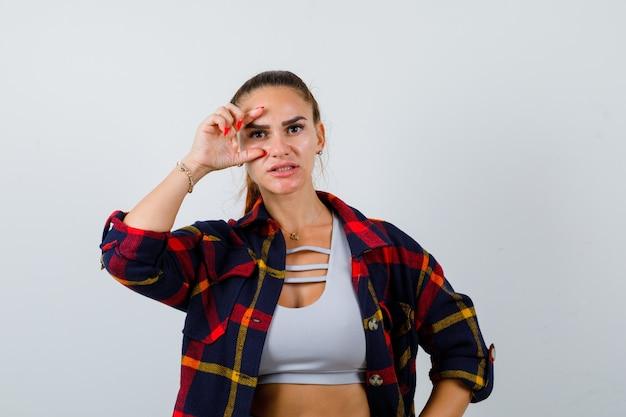 크롭 탑을 입은 젊은 여성, 체크무늬 셔츠는 손가락을 통해 보고 예쁜 앞모습을 보고 있습니다.