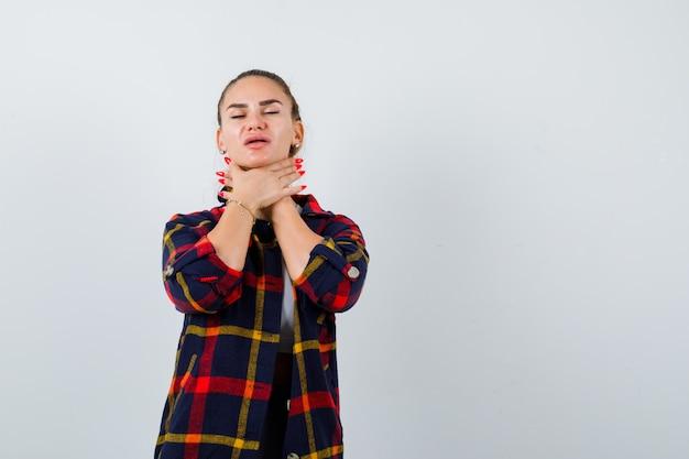 クロップトップの若い女性、市松模様のシャツ、自分を窒息させて絶望的に見えるパンツ、正面図。