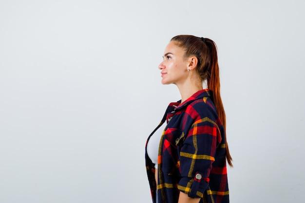 Молодая женщина в кроп-топе, клетчатой рубашке, штанах смотрит в сторону и выглядит уверенно, вид спереди.