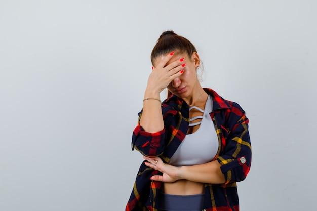 크롭 탑을 입은 젊은 여성, 체크무늬 셔츠, 이마에 손을 얹고 지쳐 보이는 바지, 전면 전망.