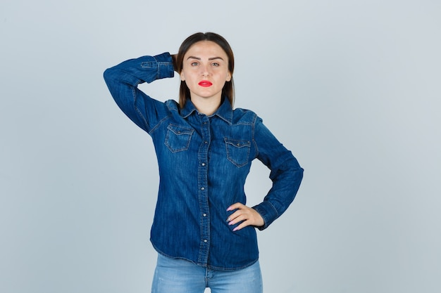 デニムシャツとジーンズの若い女性は、腰に手を保ち、自信を持って見ながら頭の後ろで手をつないでいます