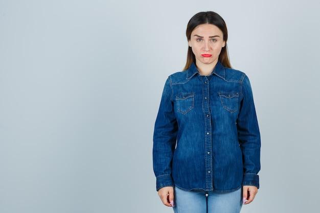 Молодая женщина в джинсовой рубашке и джинсах смотрит спереди и обижается