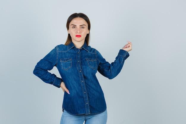 デニムシャツとジーンズの若い女性が腰に手を保ち、魅力的に見えるようにポーズをとる