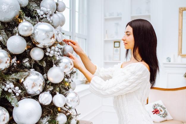 クリスマスツリーの横にあるドレスの若い女性