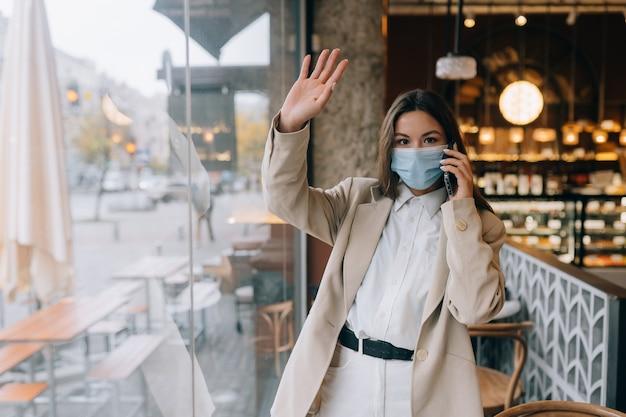 検疫中にカフェでフェイスマスクの若い女性。検疫で働くビジネスウーマン。女性は電話で話します。 covid-19