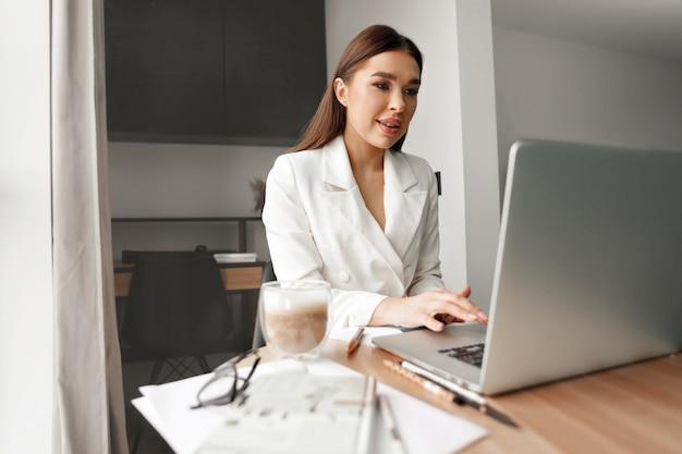 노트북을 사용하는 안경을 쓴 젊은 여성, 집에 있는 고객과 인터넷에서 통신, 테이블에 커피 머그잔. 아늑한 사무실 직장, 원격 작업, 전자 학습 개념
