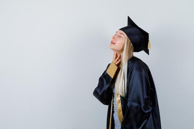 彼女の首の皮膚を調べて繊細に見える大学院の制服を着た若い女性。