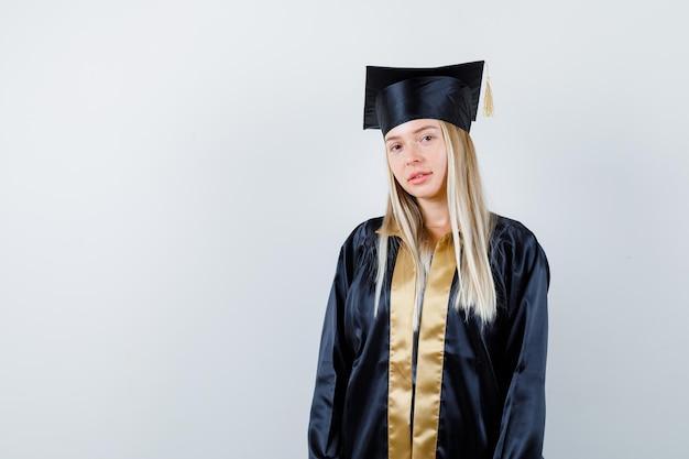 대학원 제복을 입은 젊은 여성이 카메라를보고 현명하게보고