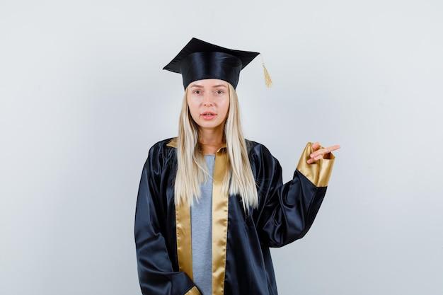 Молодая женщина в униформе выпускника, указывающая вправо и выглядящая разумной
