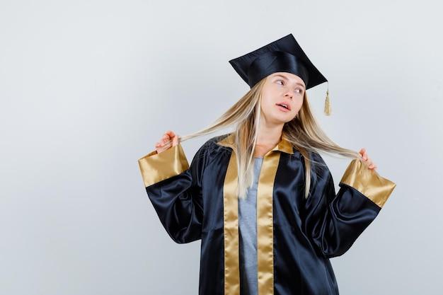 그녀의 머리카락을 잡고 매혹적인 찾고있는 동안 포즈를 취하는 대학원 제복을 입은 젊은 여성