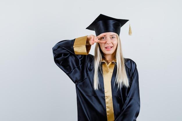 目にvサインを示し、幸せそうに見える大学院の制服を着た若い女性