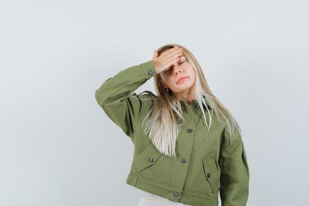 그녀의 이마에 손을 잡고 피곤, 전면보기를 찾고 녹색 재킷에 젊은 여성.