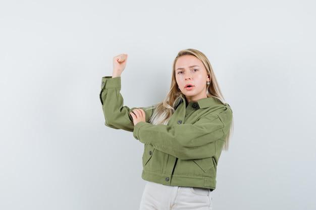 緑のジャケットを着た若い女性、ジーンズは彼女の腕の筋肉をチェックし、焦点を合わせて、正面図を探しています。