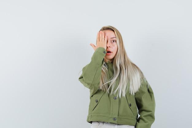 緑のジャケットを着た若い女性、ジーンズは彼女の顔の半分を手で覆い、不安そうに見える、正面図。