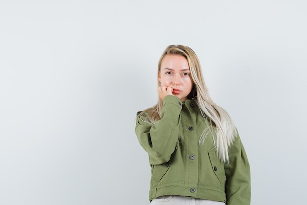 녹색 재킷, 청바지 카메라, 전면보기에 초점을 맞춘 젊은 여성.