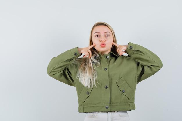 緑のジャケットを着た若い女性、唇をふくれっ面しながら彼女の頬を指しているジーンズ、正面図。