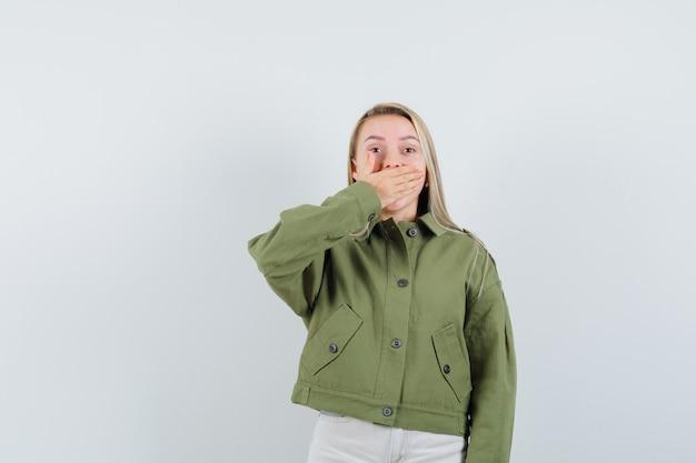 녹색 자 켓, 입에 손으로 하 품 하 고 졸려, 전면보기 청바지에 젊은 여성.