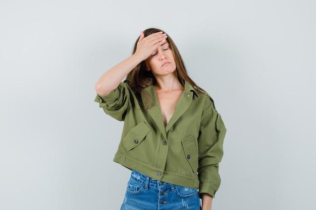 녹색 재킷에 젊은 여성, 반바지 이마에 손을 잡고 피곤 찾고, 전면보기.