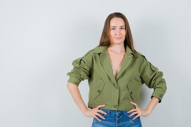 녹색 재킷에 젊은 여성, 서서 멋진, 전면보기를 보면서 포즈를 취하는 반바지.