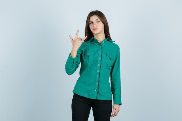 緑のシャツを着た若い女性、ロックジェスチャーを示し、誇らしげに見えるパンツ、正面図。